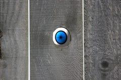 Globo del ojo azul que mira en agujero de nudo directo en una cerca de madera. Imagen de archivo libre de regalías