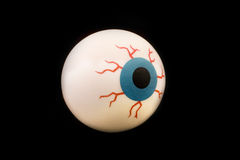 Globo del ojo de goma del juguete aislado sobre negro Imágenes de archivo libres de regalías