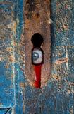 Globo del ojo que mira fijamente a través del ojo de la cerradura oxidado Imagen de archivo libre de regalías