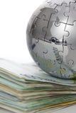 Globo del rompecabezas del metal con el dinero Imágenes de archivo libres de regalías