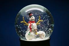 Globo della neve di inverno con il pupazzo di neve sul blu Fotografie Stock