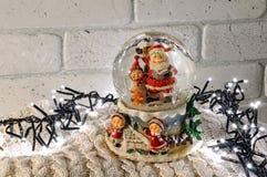 Globo della neve di Natale con il Babbo Natale dentro e le luci della ghirlanda Immagine Stock Libera da Diritti