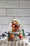 Globo della neve di Natale con il Babbo Natale dentro e le luci della ghirlanda Immagini Stock Libere da Diritti