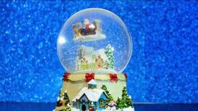 Globo della neve di Natale con il fiocco di neve Il ricordo di vetro del nuovo anno sul fondo vago blu delle luci di scintillio archivi video