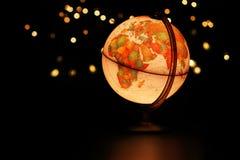 Globo della terra che emette luce in cielo stellato scuro Fotografia Stock