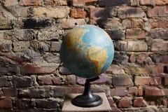 Globo della terra su un fondo del muro di mattoni immagini stock
