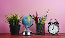 Globo, despertador, planta y escuela del mundo inmóviles en cesta Fotos de archivo libres de regalías