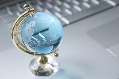 Globo di cristallo sul computer portatile Immagine Stock Libera da Diritti