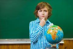 Globo di pensiero della tenuta del ragazzo sul fondo della lavagna Concetto della scuola ed educativo Fotografia Stock Libera da Diritti