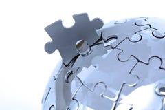 Globo di puzzle del metallo su priorità bassa bianca fotografia stock