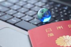 Globo di vetro e un passaporto sopra la tastiera Fotografia Stock