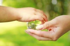 Globo di vetro nella mano di un genitore e di un bambino Immagini Stock Libere da Diritti