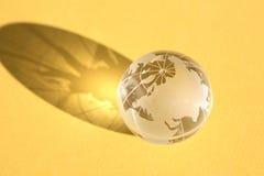 Globo di vetro su colore giallo Immagini Stock