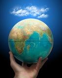 Globo a disposición con las nubes Imagen de archivo libre de regalías