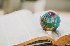 Globo do mundo no livro Conceito da escola da educação imagens de stock