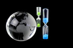 Globo e hourglass de cristal no fundo preto imagens de stock