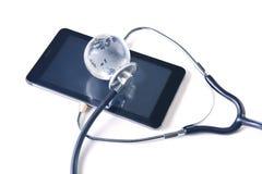 Globo e stetoscopio di vetro sulla compressa Fotografia Stock Libera da Diritti