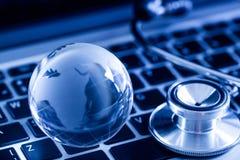 Globo e stetoscopio di vetro sulla tastiera di computer Immagine Stock Libera da Diritti