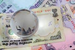 Globo em notas indianas das rupias da moeda Foto de Stock