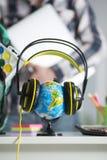 Globo en auriculares e individuo con el ordenador portátil en manos Fotografía de archivo libre de regalías