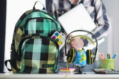 Globo en auriculares e individuo con el ordenador portátil en manos Imagen de archivo