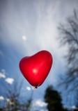 Globo en forma de corazón rojo en cielo Fotografía de archivo