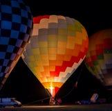Globo hermoso y colorido del aire caliente listo para el despegue en la noche imagen de archivo