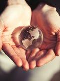 Globo modelo del cristal que se sostiene en manos con cuidado Fotos de archivo libres de regalías