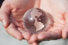 Globo modelo del cristal que se sostiene en manos con cuidado Foto de archivo libre de regalías