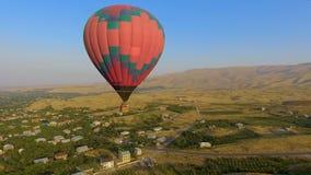 Globo multicolor enorme del aire caliente que vuela sobre el pueblo armenio, paisaje metrajes