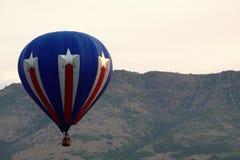 Globo patriótico del aire caliente en el cielo de la montaña imagenes de archivo