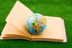 Globo perto de um caderno Imagens de Stock Royalty Free