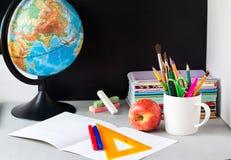 Globo, pila del taccuino e matite sulla tavola Accessori di studi dello studente e dello scolaro Di nuovo al concetto del banco immagini stock libere da diritti