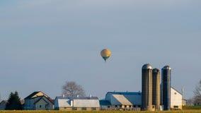 Globo que flota sobre una casa de la granja de Amish, el condado de Lancaster, PA del aire caliente fotos de archivo