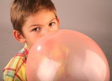 Globo que sopla del niño Foto de archivo libre de regalías