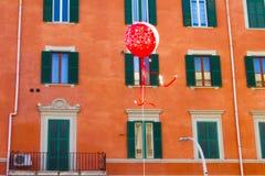 Globo rojo con el edificio anaranjado en fondo imagen de archivo