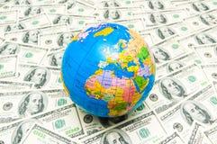 Globo sopra le banconote americane del dollaro Fotografia Stock Libera da Diritti