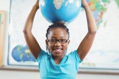 Globo sorridente della tenuta dell'allievo davanti alla mappa di mondo Fotografia Stock Libera da Diritti