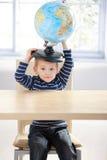 Globo sveglio della holding del ragazzino sulla testa Fotografia Stock