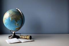 Globo y libro de ejercicio en el escritorio del estudiante Imagenes de archivo