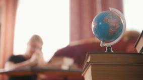 Globo y libros en el escritorio almacen de metraje de vídeo