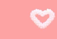 Globos blancos bajo la forma de corazón en un fondo rosado Imagen de archivo libre de regalías