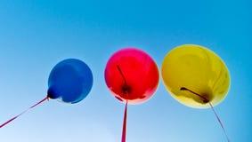 Globos coloreados en el cielo azul Fotografía de archivo libre de regalías