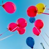 Globos coloreados en el cielo azul Fotografía de archivo