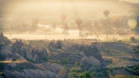 Globos coloreados sobre el valle de Cappadocia cubierto por la niebla de la mañana Foto de archivo libre de regalías