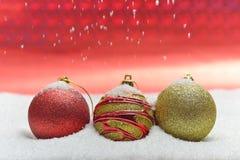 Globos coloridos de la Navidad rodeados por la nieve Fotografía de archivo