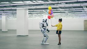Globos coloridos de los regalos amistosos de la muchacha a un cyborg blanco almacen de video