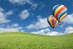 Globos coloridos del aire caliente en cielo azul hermoso sobre campo de hierba Fotos de archivo libres de regalías
