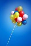 Globos coloridos en cielo azul Imágenes de archivo libres de regalías