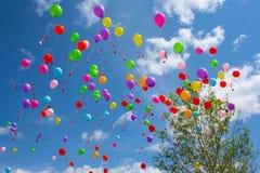 Globos coloridos lanzados en cielo azul Fotografía de archivo